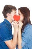 亲吻在红色心脏后的美好的年轻愉快的夫妇,举行它在手上,隔绝在白色背景 图库摄影