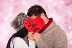 亲吻在红色心脏后的年轻夫妇的综合图象 免版税库存图片