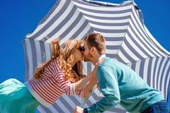 亲吻在蓝天的伞下的年轻夫妇 免版税库存照片