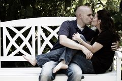亲吻在长凳的夫妇 免版税库存图片