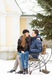 亲吻在长凳的恋人 免版税库存照片