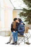 亲吻在长凳的恋人 免版税库存图片