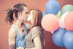亲吻在颜色背景的愉快和滑稽的夫妇迅速增加 免版税库存图片