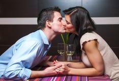 亲吻在餐馆的年轻夫妇 免版税库存图片