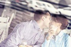 亲吻在餐馆的年轻夫妇 免版税库存照片