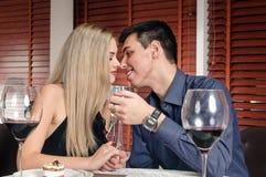 亲吻在餐馆的年轻夫妇 免版税图库摄影