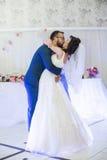 亲吻在他们的第一个舞蹈期间的愉快的新婚佳偶夫妇在weddin 免版税库存图片