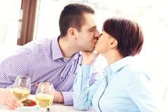 亲吻夫妇在餐馆 免版税库存图片