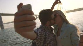 亲吻年轻夫妇拍摄照片反对明亮地发光的太阳和闪烁的河