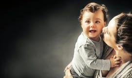 亲吻女儿的母亲的画象 免版税库存图片