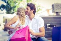亲吻她微笑的男朋友的妇女在接受礼物以后 免版税库存照片