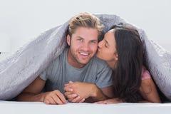 亲吻她的丈夫的妇女 免版税库存照片