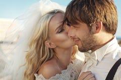 亲吻她的丈夫的年轻新娘的浪漫图片 免版税库存图片