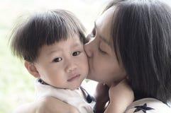 亲吻她的儿子的年轻母亲 库存图片