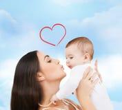 亲吻她的孩子的愉快的母亲 免版税库存照片
