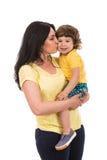 亲吻她的小孩儿子的母亲 图库摄影