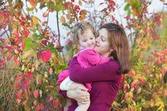 亲吻她的小孩女儿的母亲在庭院里 库存照片