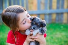 亲吻她的小狗奇瓦瓦狗小狗的儿童女孩 免版税库存图片