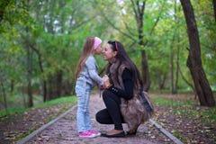 亲吻她的母亲的鼻子的逗人喜爱的小女孩 库存图片