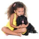 亲吻她的爱犬的逗人喜爱的小女孩 库存图片