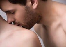 亲吻她的肩膀。亲吻他的英俊的年轻人特写镜头  图库摄影