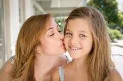 亲吻她的面颊的母亲女儿。 免版税图库摄影