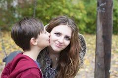 亲吻她的面颊的男孩十几岁的女孩 免版税图库摄影