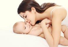 亲吻她的婴孩的愉快的年轻爱恋的母亲 免版税库存图片