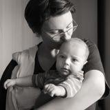 亲吻她的婴孩的美丽的母亲 免版税库存照片
