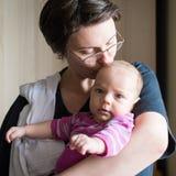 亲吻她的婴孩的美丽的母亲 免版税库存图片