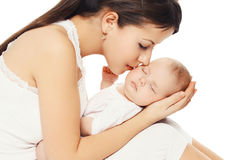 亲吻她的婴孩的年轻爱恋的母亲画象  免版税库存图片