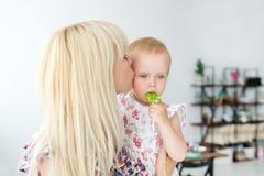 亲吻她的婴孩` s的母亲 拿着婴儿` s的母亲 一个母亲的画象有婴孩的在家 库存图片