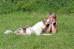 亲吻她的年轻所有者的大牧羊犬狗 库存图片