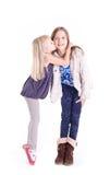 亲吻她的更老的姐妹的小女孩 免版税图库摄影