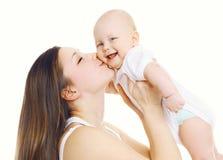 亲吻她逗人喜爱的婴孩的年轻妈妈 免版税库存照片