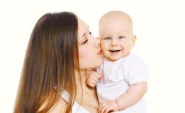 亲吻她逗人喜爱的婴孩的画象愉快的母亲 库存照片