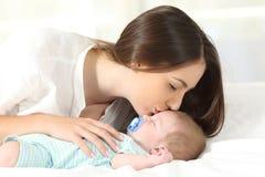 亲吻她婴孩睡觉的富感情的母亲 免版税库存照片