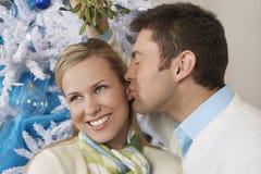 亲吻妇女的人在槲寄生下 图库摄影