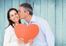 亲吻妇女的成熟人拿着红色心脏 库存照片