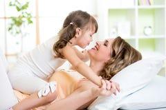 亲吻妈妈和儿童的女儿拥抱和  免版税图库摄影