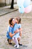 亲吻妈妈的女孩 免版税库存照片