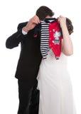 亲吻婚礼加上婴孩衣裳:怀孕和婚姻 免版税库存照片