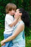 亲吻他鼻子的爱恋的儿子愉快的母亲 免版税图库摄影
