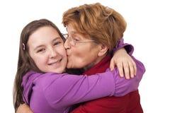 亲吻孙女的祖母 免版税库存图片
