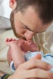 亲吻婴孩的父亲 免版税库存图片