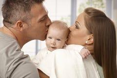 亲吻婴孩的头的父母 免版税库存照片