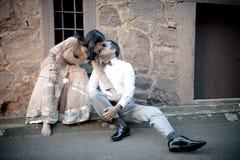 亲吻对石墙的年轻美好的印地安夫妇户外 免版税库存照片