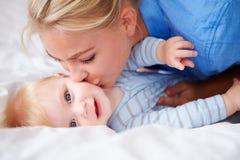 亲吻小儿子的母亲,他们在床上一起在 库存图片