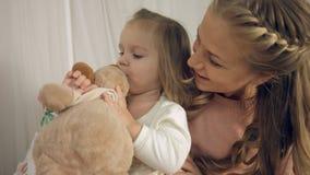 亲吻小女儿和他们的玩具的母亲 免版税图库摄影