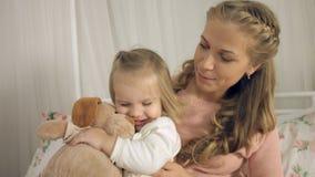 亲吻小女儿和他们的玩具的母亲 免版税库存照片